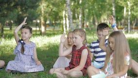 Kinder und Ausbildung, junge Frau bei der Arbeit als Erzieherlesebuch zu den Jungen und Mädchen im Park stock footage