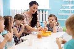 Kinder und Betreuer essen zusammen Früchte im Kindergarten oder im Kindertagesstätte stockfotografie