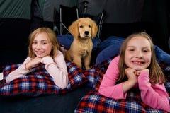 Kinder und ein Welpe, der in einem Zelt kampiert Lizenzfreie Stockfotografie