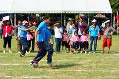 Kinder und Eltern, die eine Teamwork läuft am Kindergartensporttag tun Lizenzfreies Stockbild