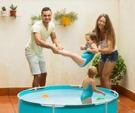 Kinder und Eltern, die im Pool spielen Stockbild