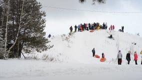 Kinder und Erwachsene gleiten auf dem Schneeschläuche stock video footage
