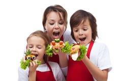 Kinder und Frau, die einen Biss von lustigen Geschöpfsandwichen nehmen Stockfotos