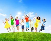 Kinder und Frauen, die draußen Arme anheben Lizenzfreies Stockfoto
