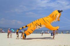 Kinder und gelber Katzendrachen auf dem Strand Stockfotos