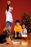 Kinder und Hund, die durch Weihnachtsbaum sitzen Lizenzfreies Stockbild