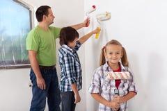 Kinder und ihr Vater, die einen Raum malen Stockbild
