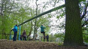 Kinder-und Jugendlich-Spiel im Schwingen im Park stock footage