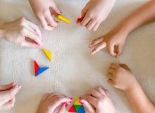 Kinder und Lehrer, die zusammen Tangram spielen lizenzfreies stockfoto