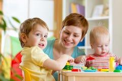 Kinder und Mutter, die buntes Lehmspielzeug spielen Stockfotografie