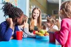 Kinder und Pflegekraft essen Frucht zusammen stockfotos