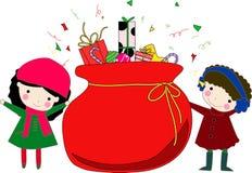 Kinder und Weihnachtsbeutel mit Geschenken Lizenzfreie Stockfotos