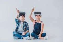 Kinder unter Verwendung der Kopfhörer der virtuellen Realität und mit dem Finger beim Sitzen oben zeigen auf dem Boden Lizenzfreie Stockfotografie