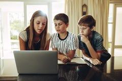 Kinder unter Verwendung der Laptop-Computers für das Lernen lizenzfreie stockfotos