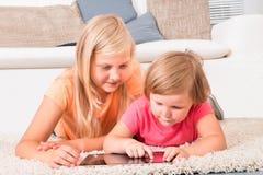 Kinder unter Verwendung der Tablette, die auf Teppich liegt Stockbilder