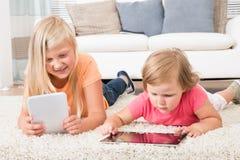 Kinder unter Verwendung der Tablette, die auf Teppich liegt Stockfotos