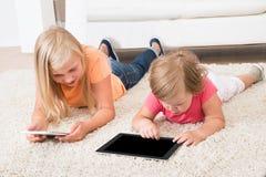 Kinder unter Verwendung der Tablette, die auf Teppich liegt Lizenzfreie Stockfotos