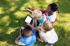 Kinder unter Verwendung der Technologie während eines sonnigen Tages Lizenzfreies Stockbild