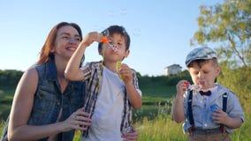 Kinder-Verhältnisse, nette kleine Jungen mit Schlagseifenblasen der Jugendlichen auf Wiese stock video footage