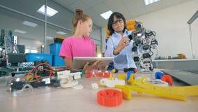 Kinder versuchen, einen Roboter auf einer Tabelle, unter Verwendung der Werkzeuge herzustellen 4K stock video footage