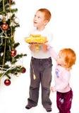 Kinder verzieren einen Neujahr Baum Stockfotografie