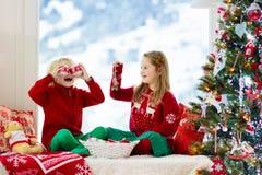 Kinder verzieren Weihnachtsbaum Kind auf Weihnachtsvorabend stockbilder