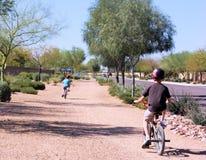 Kinder, welche die Fahrräder tragen Sturzhelme reiten Stockbild