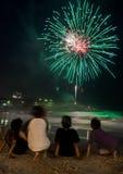 Kinder, welche die Feuerwerke durch den Strand auf Sylvesterabend aufpassen stockfoto