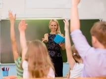 Kinder, welche die Hände kennen die Antwort zur Frage anheben Lizenzfreies Stockfoto