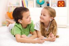 Kinder, welche die Kopfhörer hören Musik teilen stockfotografie