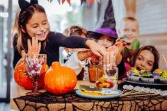 Kinder, welche die Kostüme setzen ihre Hände in Glas mit gummiartigen Würmern tragen stockfotos
