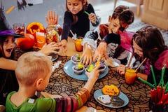 Kinder, welche die Kostüme sich fühlen nett tragen, Halloween im Kindergarten feiernd stockbild