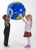 Kinder, welche die Kugel unterstützen Lizenzfreie Stockbilder