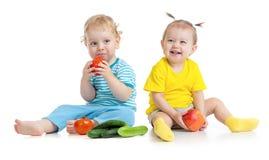 Kinder, welche die Obst und Gemüse lokalisiert essen stockbilder