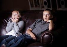 Kinder, welche die schockierende Fernsehprogrammierung sich ansehen Stockfotografie