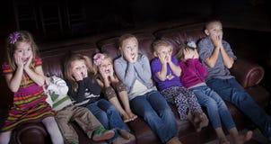 Kinder, welche die schokierende Fernsehen-Programmierung sich ansehen Stockfoto