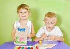 Kinder werden von farbigem Lehm geformt Stockbild