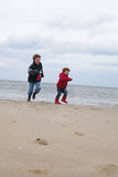 Kinder am Winterstrand Stockbilder
