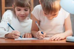 Kinder zeichnen am Tisch Stockbilder