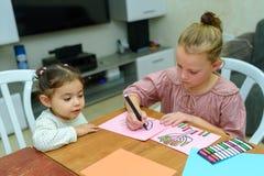 Kinder zeichnen und spielen mit Aufklebern Das Spielen mit Aufklebern kann Kind auf wichtigen Entwicklungsbereichen helfen stockfotos