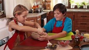 Kinder zu Hause, die eine Pizza machen stock footage