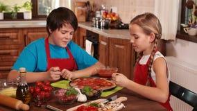 Kinder zu Hause, die Pizza - Schmecken der Soße machen stock video