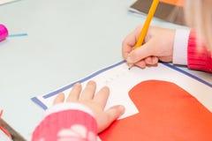 Kinderabgehobener betrag eine Postkarte Kinder nehmen an Näharbeit teil Das Mädchen unterzeichnet eine Postkarte am 14. Februar Stockbild