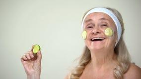 Kinderachtige positieve dame die het masker van het komkommergezicht, optimistische houding toepassen tegenover leeftijd royalty-vrije stock afbeelding