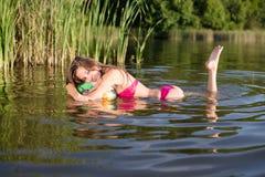kinderachtige schoonheid: beeld van glamour mooi brunette in bikini die pret het ontspannen in water op de groene zomer hebben in Stock Foto
