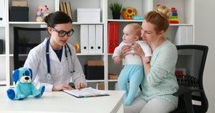 Kinderarzt, der auf Arbeitsplatz im Büro sagt geduldiger Diagnose sitzt stock video footage
