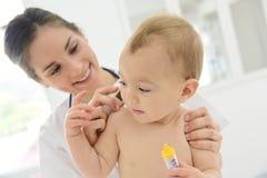 Kinderarzt, der die Temperatur des Babys nimmt Lizenzfreies Stockbild