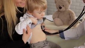 Kinderarzt, der einen kleinen Jungen durch Stethoskop überprüft stock video