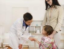 Kinderarzt, der Hand mit Mädchenkindpatienten rüttelt Lizenzfreie Stockfotos