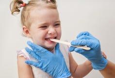 Kinderarzt, der kleines Mädchen ` s Kehle mit Zungensenker überprüft Stockbild